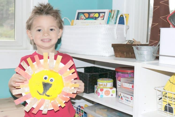 preschooler holding up paper plate lion craft