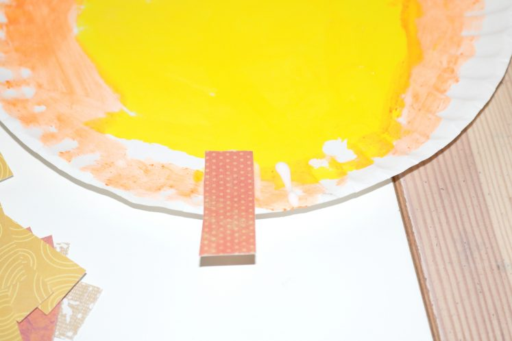 preschooler attaching patterned paper to edge of paper plate to make mane