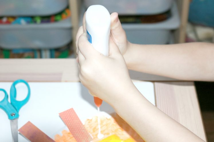 preschooler squeezing glue onto paper plate