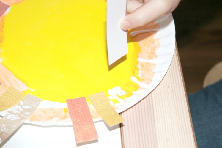 preschooler adding patterned paper around edge of paper plate to make mane