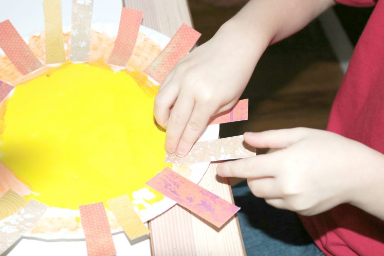 preschooler gluing orange and yellow patterned paper strips around edges of paper plate to create mane