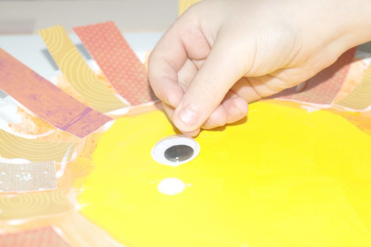 preschooler adding wiggle eyes to paper plate lion craft