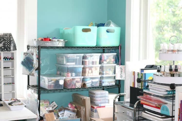 wire shelf containing several plastic containers filled with organized craft supplies