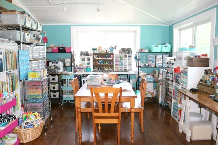 shared craft room featuring wooden table and chairs and various shelves containing craft supplies