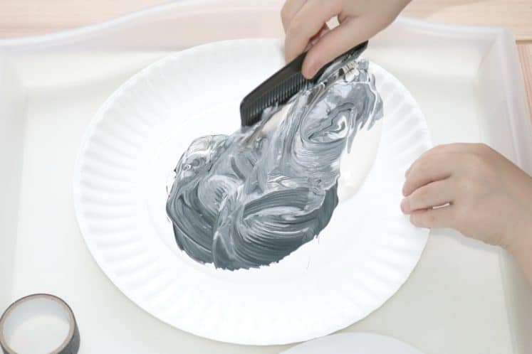preschooler mixing black and white paint with comb