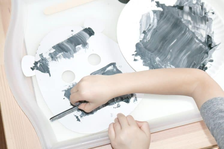 preschooler using comb to spread gray paint on gorilla mask