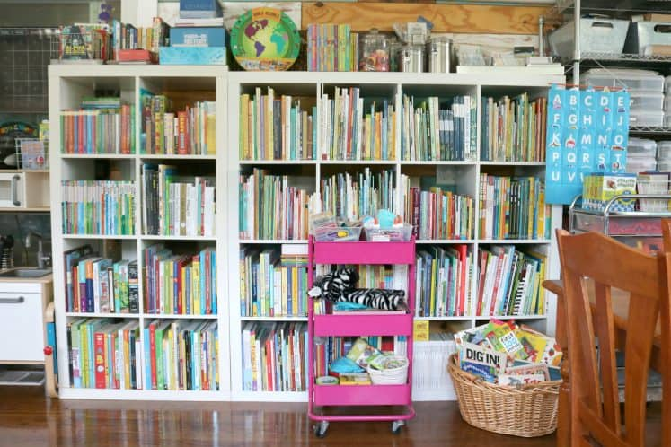 rolling cart and basket of board books in front of cube bookshelves filled with children's books