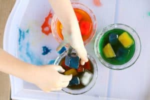 preschooler dropping colored ice cubes into dish of water