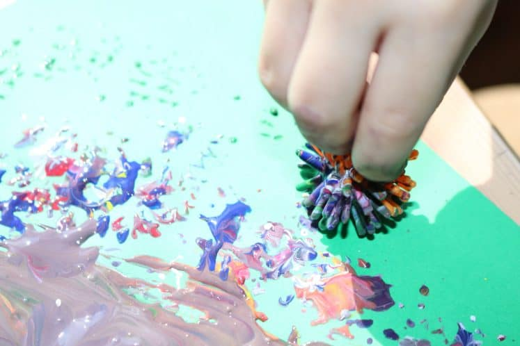 preschooler holding pokey ball covered with paint
