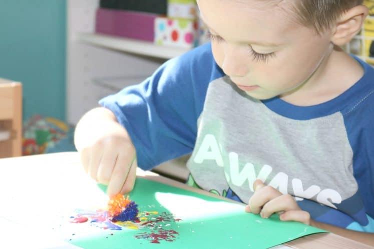 preschooler using pokey ball to paint flowers