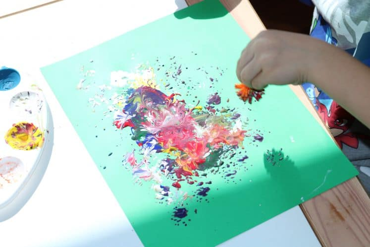 preschooler painting with pokey ball to make flowers process art