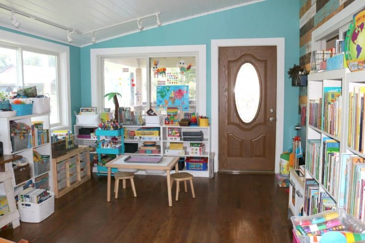 child's play area featuring sensory table and several shelves filled with toys