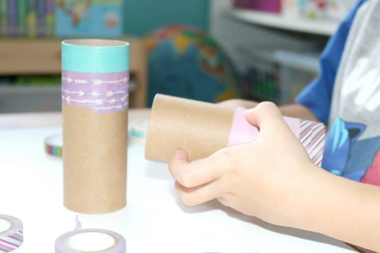 preschooler adding decorative tape to cardboard tube