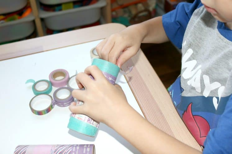 preschooler adding tape to cardboard tube