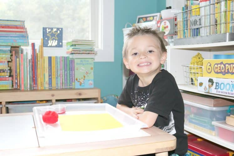 child sitting at table smiling and ready to start splatter painting process art
