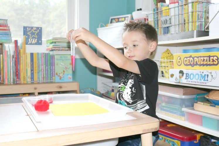child holding up eyedropper filled with paint in each hand