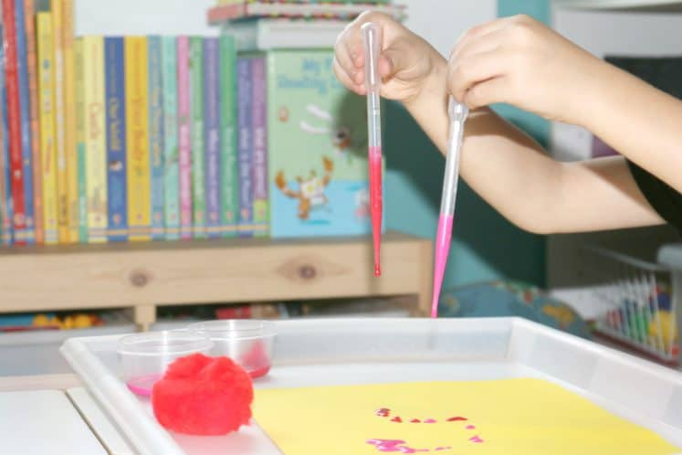 child holding two eyedroppers filled with paint over cardstock