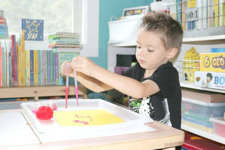 child squeezing paint onto cardstock using eyedroppers
