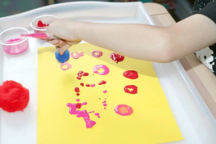 child using pompom to dab paint on cardstock