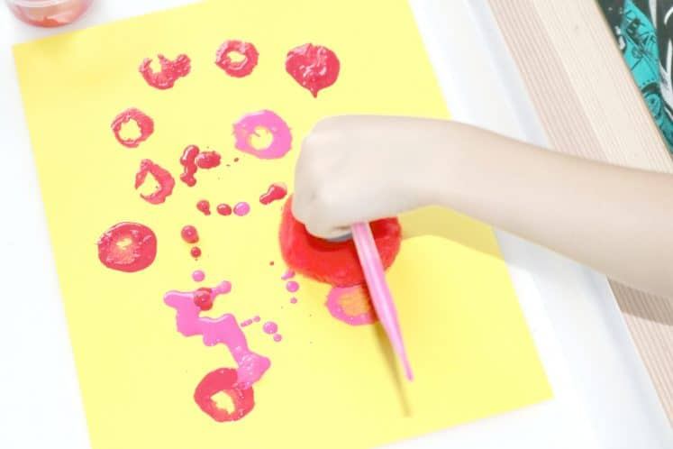 child using pompom to make large dots with paint on cardstock
