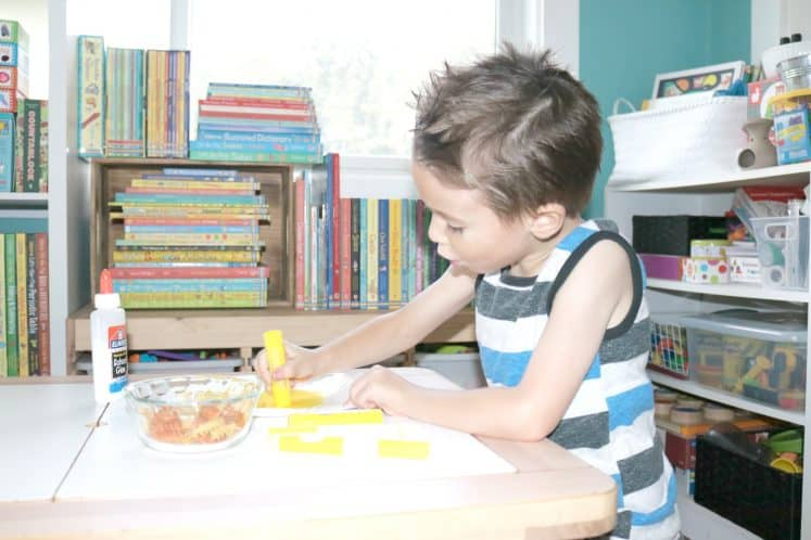 child painting paper plate to make lion craft