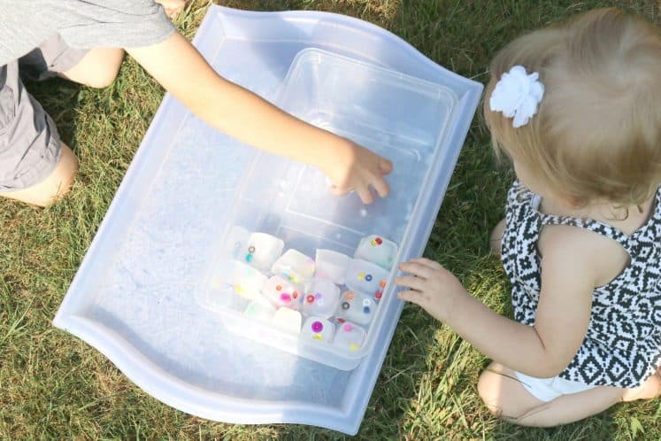 children exploring ice cubes in a plastic container