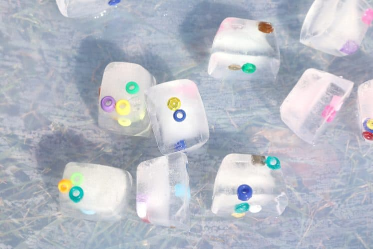 tray containing beads and sequins frozen in ice