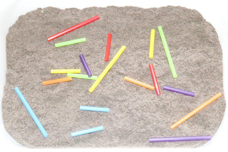 cut-up straws in sand sensory bin