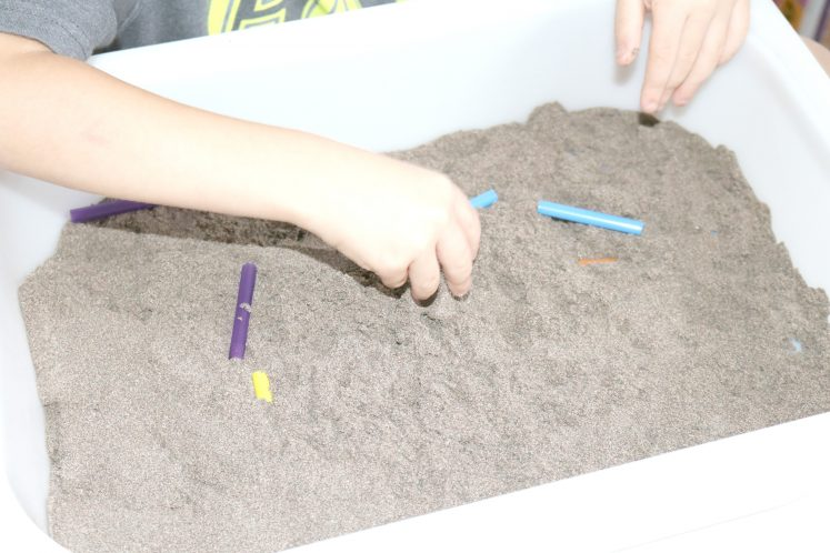 child digging in sand for straw pieces