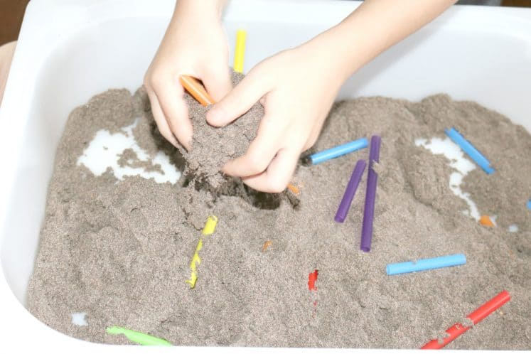 child exploring sand and straw pieces