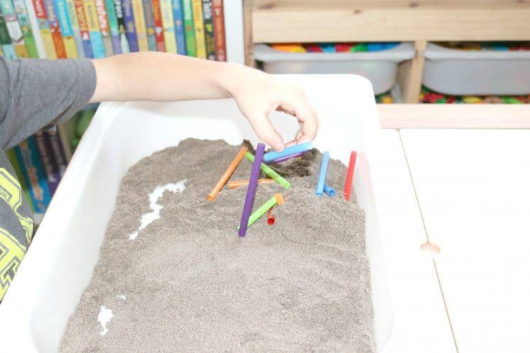 child stacking various colors of cut-up straws in sensory bin