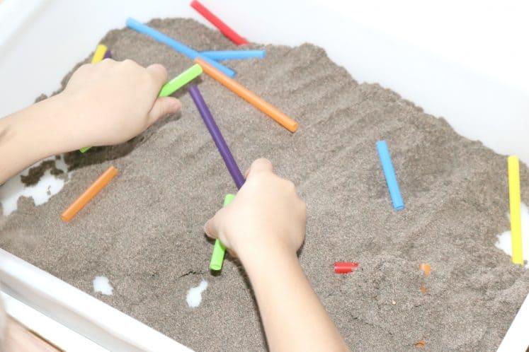 child arranging cut-up straws in sensory bin