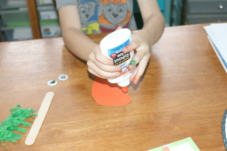 child squeezing glue onto carrot puppet