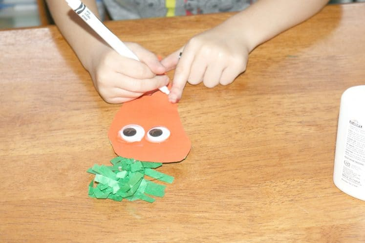 child drawing mouth on carrot puppet