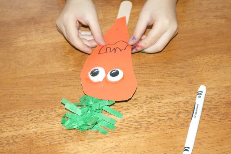 child attaching carrot puppet to craft stick