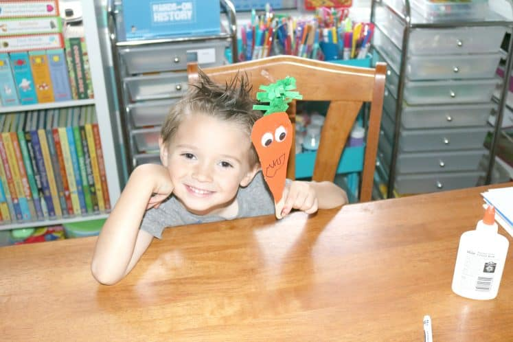 child holding up carrot puppet and smiling