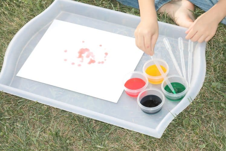 child filling eyedropper with watercolor paint