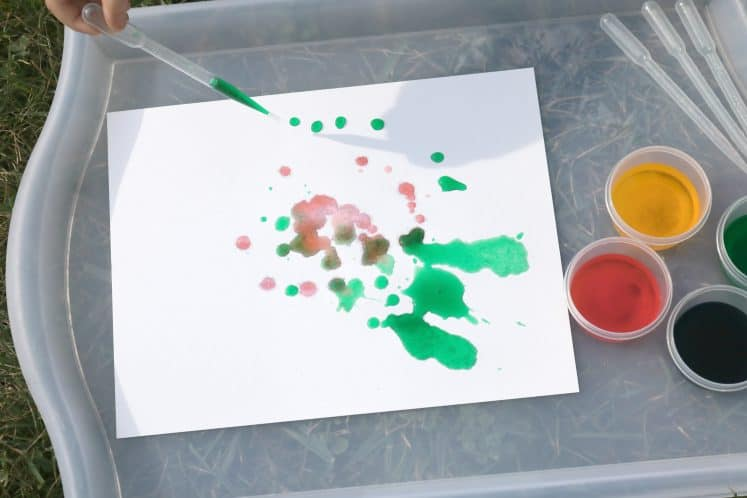child dripping green paint onto cardstock with eyedropper