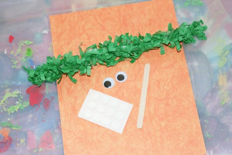 orange paper, green festoon, wiggle eyes, and craft stick on tray to make carrot puppet