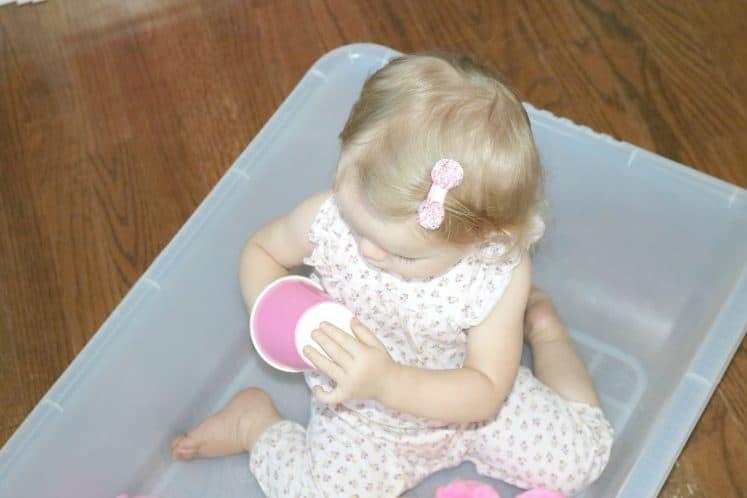toddler exploring paper cup