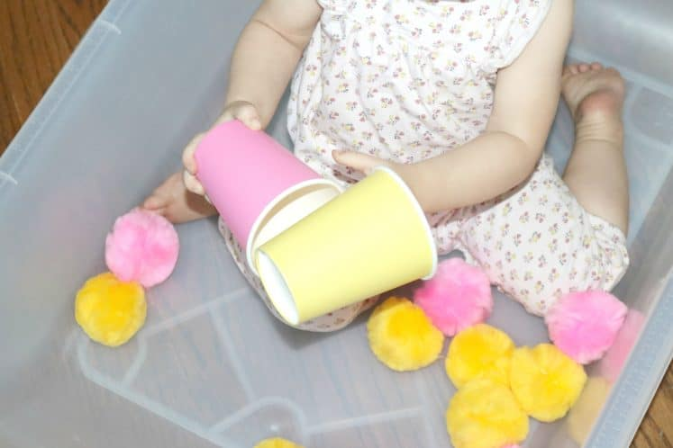 toddler holding pink cup in one hand and yellow cup in another