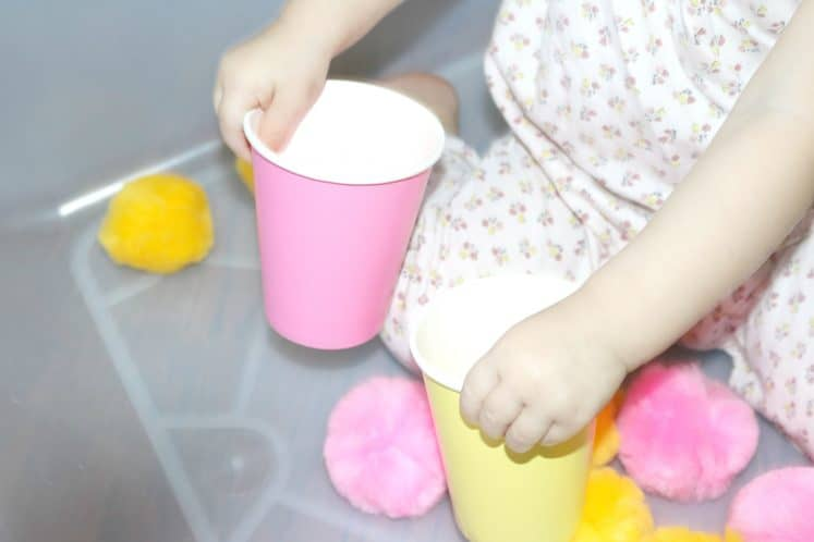 toddler holding a paper cup in each hand