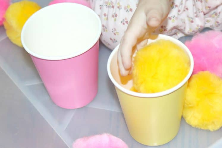 toddler putting yellow pompom into yellow paper cup