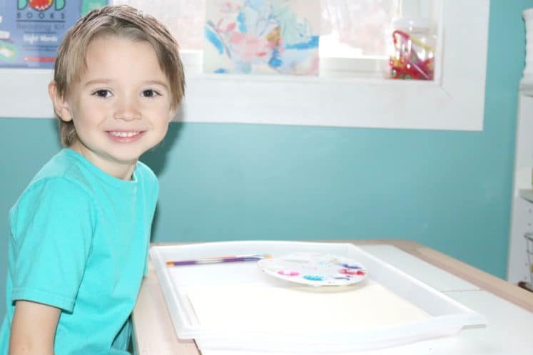 child sitting at table ready to start process art activity