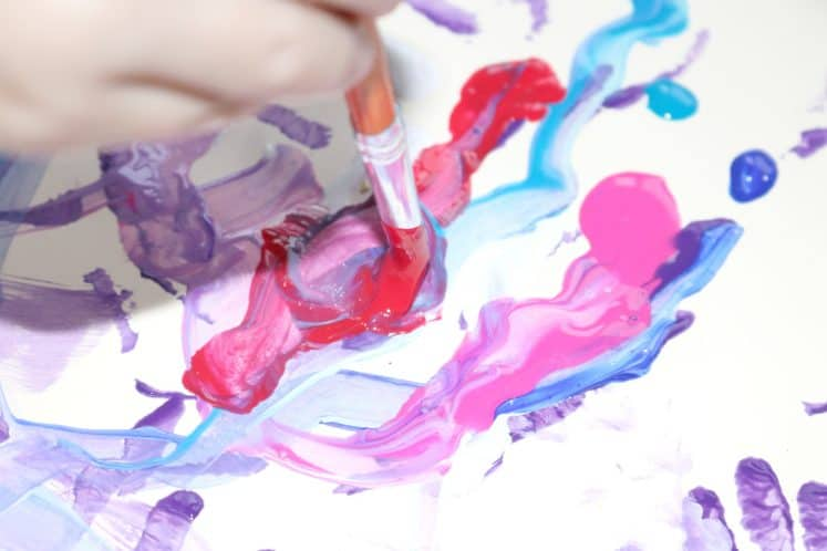 child painting with red paint