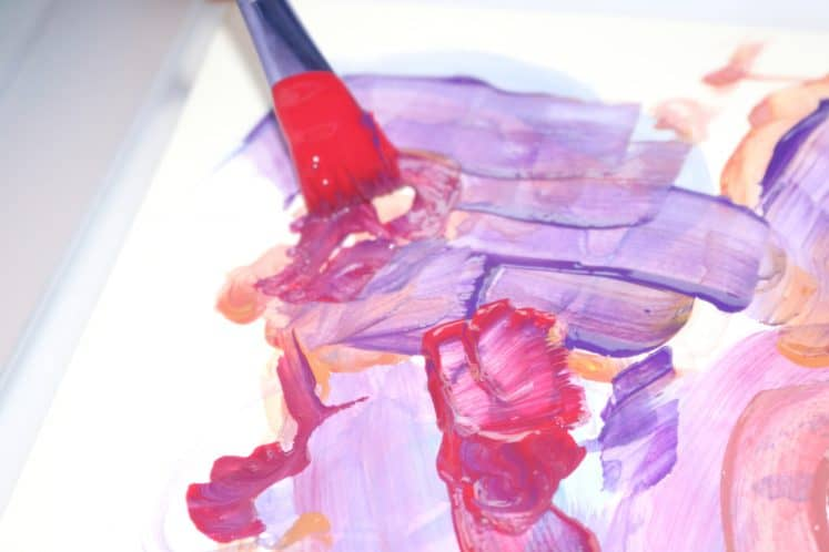 child painting on cardstock with paintbrush and pink, red, and purple paint