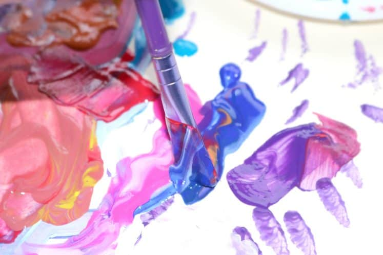 child painting with blue paint