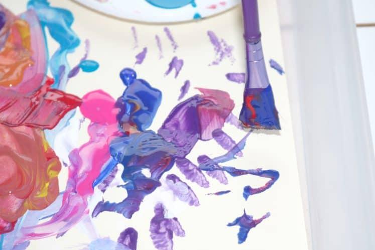 child brushing blue paint onto process art