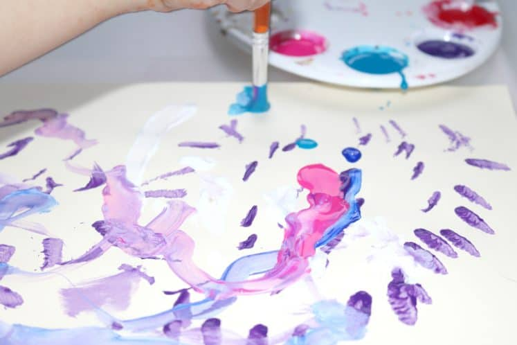 child painting on cardstock with paintbrush
