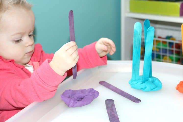 toddler exploring craft sticks and playdough